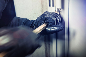 Burglar forcing door lock to gain entry