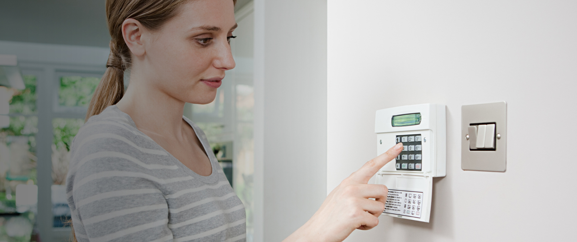 Blonde lady setting home security alarm using keypad