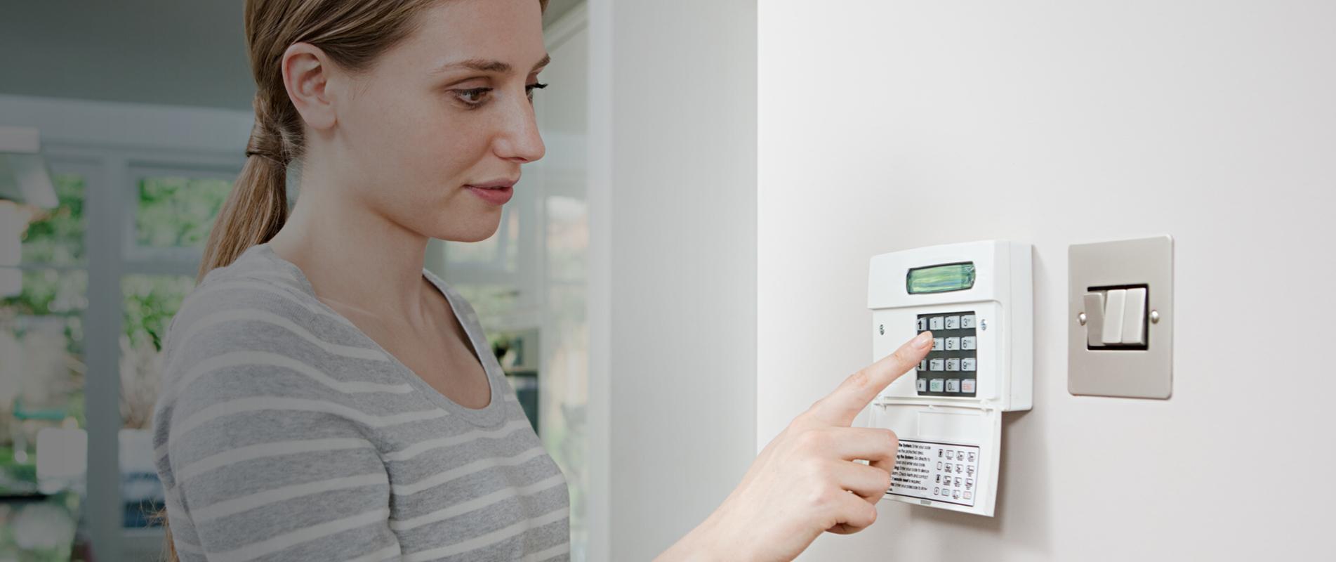 Blonde lady setting home security alarm using keypad